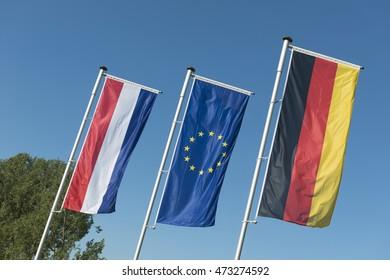Dutch flag, European Union flag and a German flag in a row