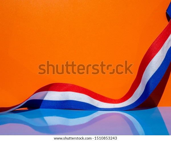Dutch flag ribbon, red white and blue on an orange background. Reflection on the blue table and room for text.