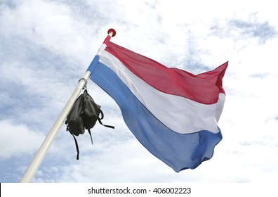 A dutch flag with a school bag in top to celebrate graduation
