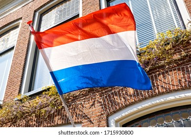A dutch flag waving in the wind on the facade of a typical dutch house on Koningsdag. A national holiday in the Kingdom of the Netherlands