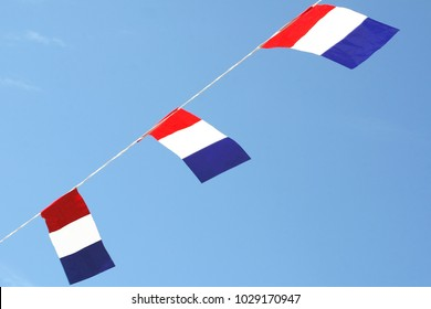 Dutch flags in blue sky, national holidays and other celebrations in the Netherlands