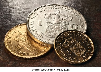 Dutch gold and silver coins on rustic wooden background