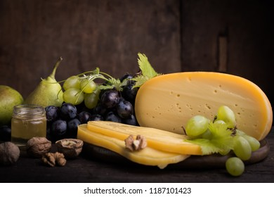 Dutch hard cheese Maasdam or Emmentaler,  with holes and grape
