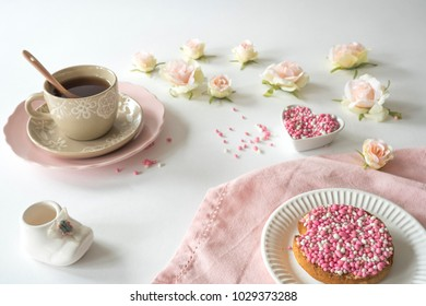 Dutch high tea celebration birth of a daughter with cup of tea and rusk with traditional food pink muisjes, aniseed, roses and baby shoe