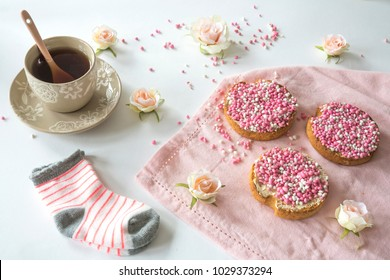 Dutch high tea celebration birth of a daughter with cup of tea and rusk with traditional food pink muisjes, aniseed, roses and baby socks