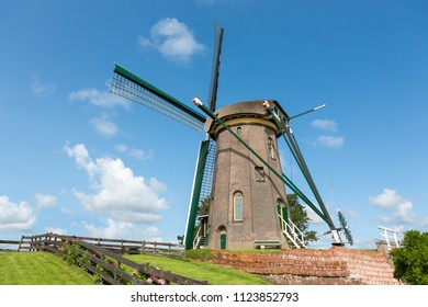 "The dutch historic windmill ""Lijkermolen"" on a dyke in the blue sky of the village of Rijpwetering."