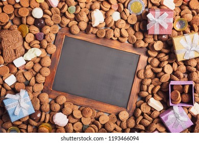 Dutch holiday Sinterklaas background with black chalkboard, gifts, pepernoten, traditional sweets strooigoed. Flat lay and copy space.