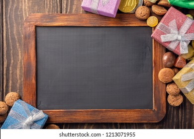 Dutch holiday Sinterklaas background with black chalkboard, gifts, pepernoten, traditional sweets strooigoed and carrots for Santa's horse. Flat lay and copy space.