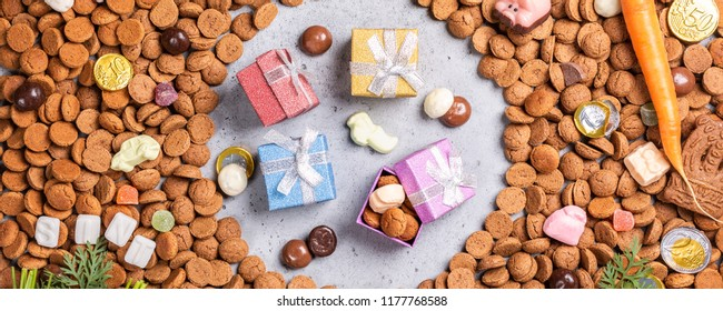 Dutch holiday Sinterklaas background with gifts, pepernoten, traditional sweets strooigoed and carrots for Santa's horse. Flat lay. Banner.