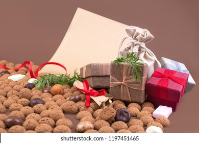Dutch holiday Sinterklaas background with pepernoten.Traditional sweets and gifts for children for the holiday. Free space for text. Top view. Copy space. Letter and gift boxes for Saint Nicholas