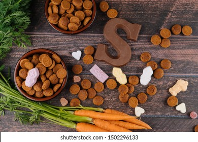 Dutch holiday Sinterklaas. Background with traditional food - pepernoten, chocolate letter, sweets strooigoed and carrots for horse. Concept for children party in Saint Nicolas day five december.