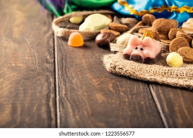 Dutch holiday 'Sinterklaas' greeting card with marzipan pig and traditional sweets kruidnoten, pepernoten for the. Festive concept with copy space.