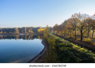 Dutch landscape with calm river and blue sky, autumn season colorful yellow and orange trees, top view in the Netherlands beauty