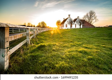 Dutch landscape with historical houses in evening along a curved road with white fence in the country - Groningen, Holland, Europe