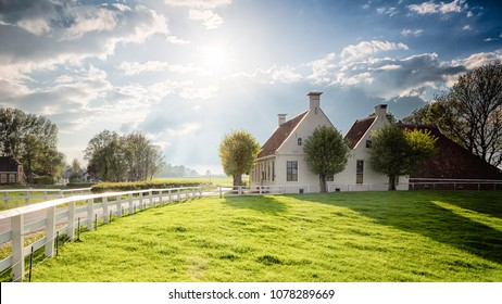 Dutch landscape with historical houses in green field with a brigh sky and sunshine and green trees - Groningen, Holland, Europe