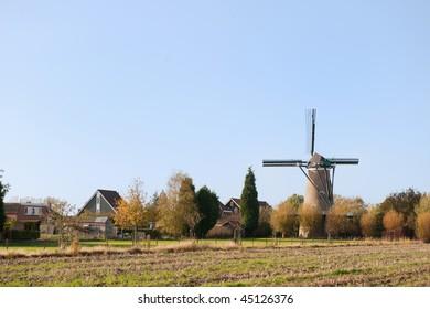 Dutch little village with windmill in landscape