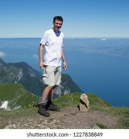 Dutch male tourist standing on le Grammont mountain with Lake Geneva on the background (Switzerland)