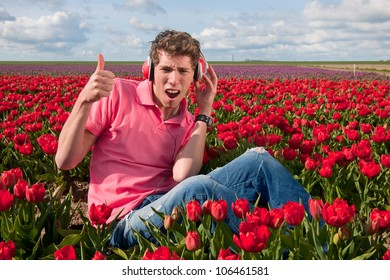 Dutch man sitting in flower fields listening to cool music