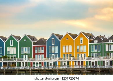 Dutch, modern, colorful vinex architecture style houses at waterside during dramatic and clouded sunset. Houten, Utrecht.