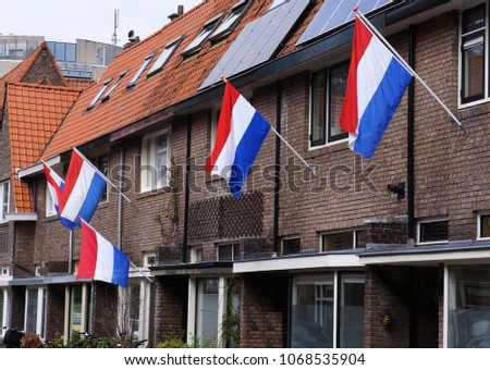 The Dutch national flag hanging near the entrance of several houses in a street in the Netherlands.