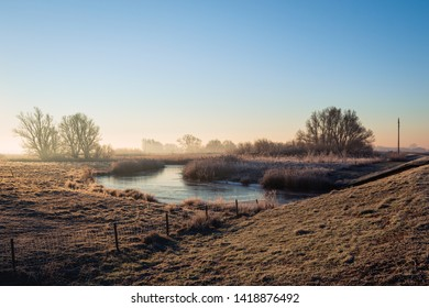 Dutch National Park Biesbosch in the winter season. It is still early in the morning and the morning mist is visible in the distance. In the background, the mast of an old sailboat is also visible.