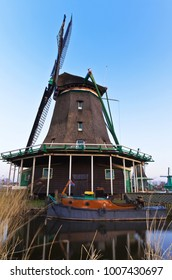 Dutch old windmill and a boat near a wooden pier on the Zaan River at a warm spring afternoon. Zaanse Schans Village. Netherlands