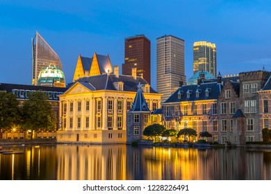 Dutch parliament building Binnenhof and Mauritshuis seen from Hofvijver at night with governmental ministry skyscraper offices in backdrop