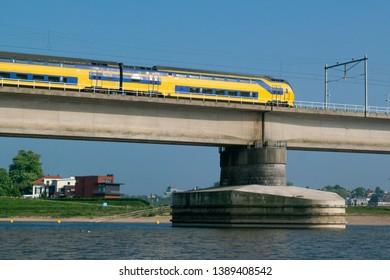 Dutch passenger train passing a bridge in Nijmegen, Gelderland