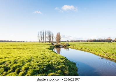 Dutch polder landscape in the fall season with a mirror smooth stream reflecting the wooden fences and two windmills in the background.