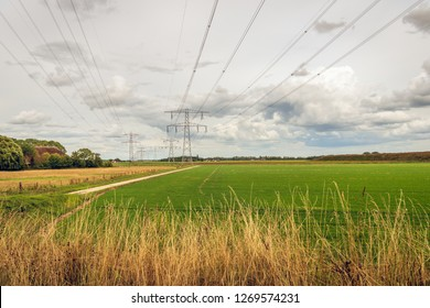 Dutch polder landscape with high voltages lines and power pylons. The photo was taken near the village of Zevenbergen, North Brabant, on a cloudy day in summertime.