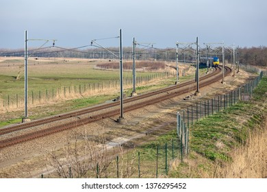 Dutch railway with approaching express train through National Park Oostvaardersplassen between Lelystad and Almere