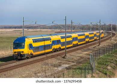 Dutch railway with double-decker express train through National Park Oostvaardersplassen between Lelystad and Almere