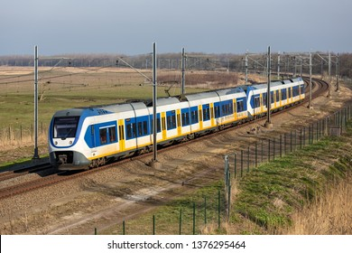 Dutch railway with local train through National Park Oostvaardersplassen between Lelystad and Almere