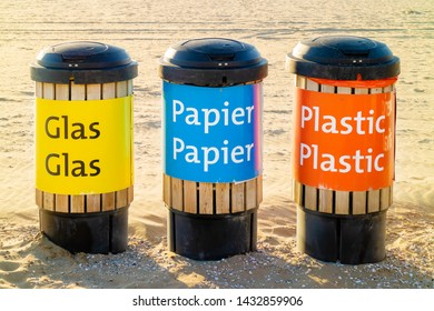 Dutch recycle waste bins for glass, paper and plastics on a beach