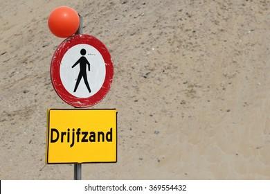 Dutch road sign: no access for pedestrians because of quicksand (translation: quicksand)