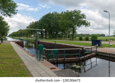 Dutch rural landscape with canal and old sluice in Friesland
