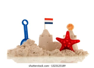 Dutch sand castle with red toys and flags isolated over white background