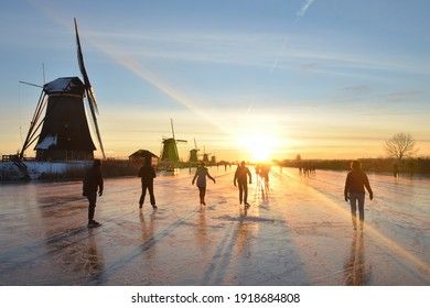 Dutch scene of skating people at the windmills of Kinderdijk at sunrise