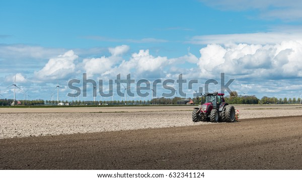 Dutch Scenery Farmer in tractor preparing land with seedbed cultivator as part of pre seeding activities in early spring season of agricultural works at farmlands, Netherlands Flevoland