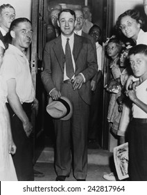 Dutch Schultz, emerging from doorway of Malone County jail, in an upstate New York town where he was on trial for federal tax evasion. 1936.