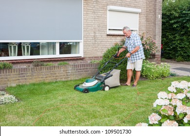 Dutch senior with serious look and mowing his front yard grass with an electric mower as spare time activity after retirement