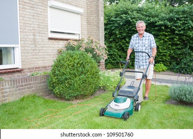 Dutch senior smiling and mowing his front yard grass with an electric mower as spare time activity after retirement