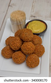Dutch snack bitterballen with mustard and cocktail picks on a white plate