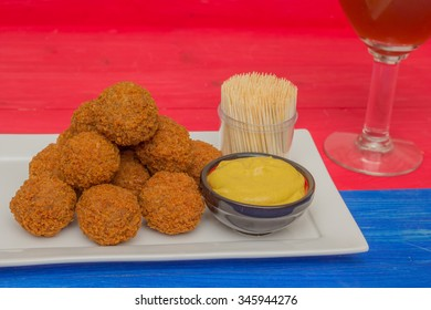 Dutch snack bitterballen with mustard and a glass of beer