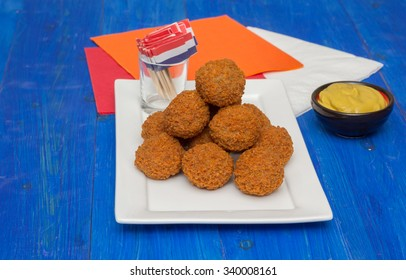 Dutch snack bitterballen with mustard on a white plate