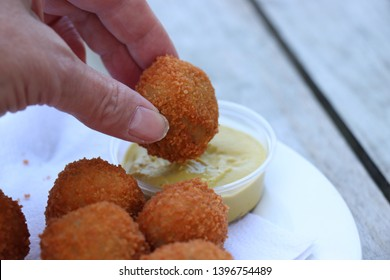 "Dutch snack:  woman eating a bitterbal with mustard. Warm stuffed fried meatballs, often served with alcoholic drinks as ""bittergarnituur"", a Dutch name for snacks"