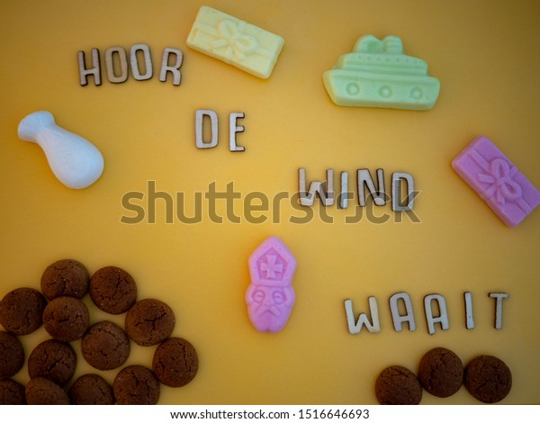 """Dutch song text meaning: """"Hear the wind is blowing"""". For the Dutch fest of Sinterklaas. With candy called pepernoten and schuimpjes on a yellow surface. Top view."""