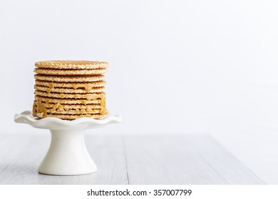 dutch stroopwafel, caramel waffle on a mini white cake stand with copy space on right