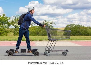Dutch teenage boy  rides on electric skateboard pushing shopping cart outdoors