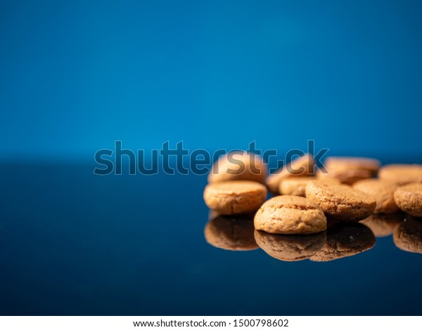 Dutch traditional candy called pepernoten for the holiday called Sinterklaas in december. Blue background with reflection.